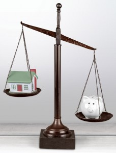 Law scales with house model and piggy bank on table background.