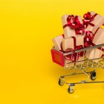 shopping cart with gifts on a yellow background. Gifts wrapped in kraft paper with a red ribbon and bow.