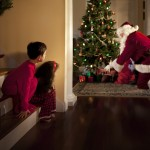 Two children peek at Santa Claus placing gifts under the Christmas tree.