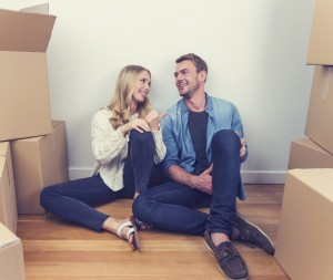 Young couple sitting in new house with packing boxes. They look like they have just moved in and they are very happy, smiling and talking. They sitting on the floor in casual clothes