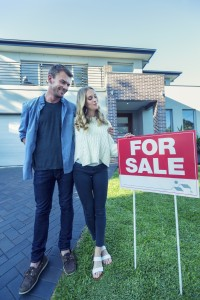 Young couple in front of a home with a For Sale sign.