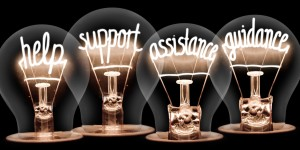 Photo of light bulbs group with shining fibers in a shape of HELP, SUPPORT, ASSISTANCE, GUIDANCE concept words isolated on black background
